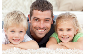 Children with father smilling to the camera in the carpet